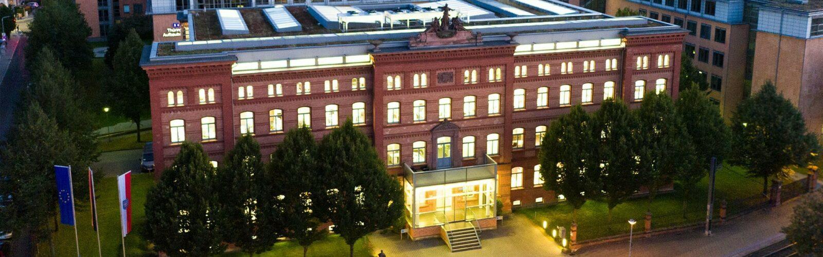 Zentrale de rTAB im Erfurter Brühl (im Bild: historisches TAB-Gebäude im Abendlicht, alle Fenster sind beleuchtet)